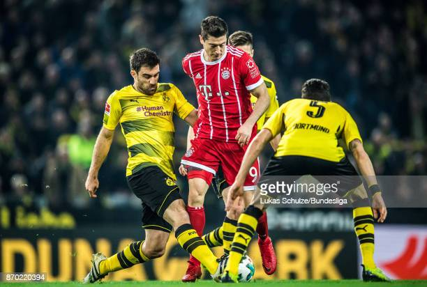 Sokratis Papastathopoulos and Marc Bartra of Dortmund tackle Robert Lewandowski of Munich during the Bundesliga match between Borussia Dortmund and...