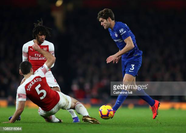 Sokratis Papastathopoulos and Mohamed Elneny of Arsenal defend from Marcos Alonso of Chelsea during the Premier League match between Arsenal FC and...