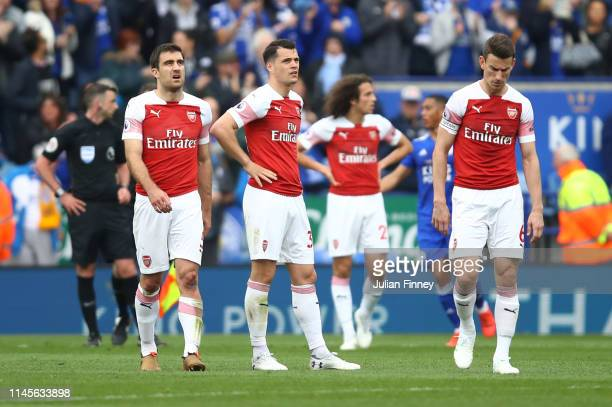 Sokratis Papastathopoulos Granit Xhaka and Laurent Koscielny of Arsenal look dejected in defeat after the Premier League match between Leicester City...