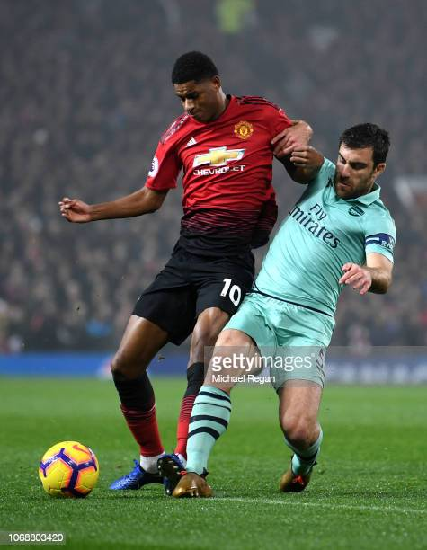 Sokratis Papastathopoulos of Arsenal battles for possession with Marcus Rashford of Manchester United during the Premier League match between...
