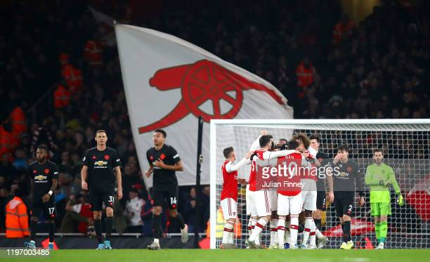 Sokratis Papastathopoulos of Arsenal celebrates with his team mates after scoring his team's second goal during the Premier League match between...