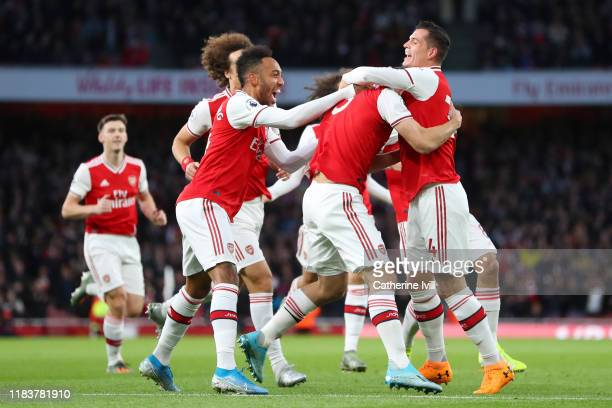 Sokratis Papastathopoulos of Arsenal celebrates with team mates Granit Xhaka of Arsenal and PierreEmerick Aubameyang of Arsenal after scoring their...