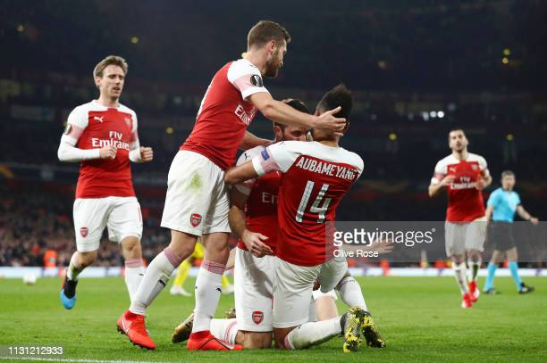 Sokratis Papastathopoulos of Arsenal celebrates with teammates after scoring his team's third goal during the UEFA Europa League Round of 32 Second...