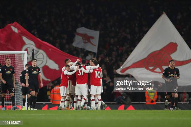 Sokratis Papastathopoulos of Arsenal celebrates with teammates after scoring a goal to make it 20 during the Premier League match between Arsenal FC...