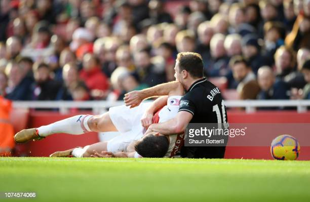 Sokratis Papastathopoulos of Arsenal clashes with Ashley Barnes of Burnley during the Premier League match between Arsenal FC and Burnley FC at...