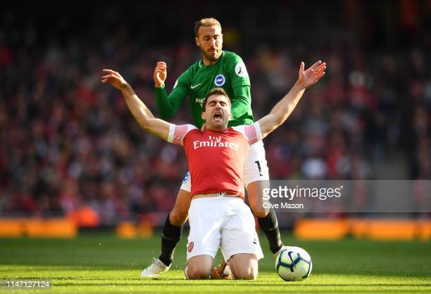 Sokratis Papastathopoulos of Arsenal is challenged by Glenn Murray of Brighton and Hove Albion during the Premier League match between Arsenal FC and...