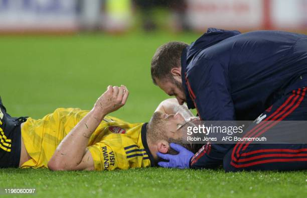 Sokratis Papastathopoulos of Arsenal is taken off after being trated for a head injury during the Premier League match between AFC Bournemouth and...