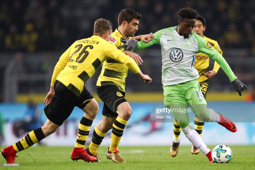 Sokratis Papastathopoulos #25 of Borussia Dortmund and Divock Origi #14 of VfL Wolfsburg battle for the ball during the Bundesliga match between Borussia Dortmund and VfL Wolfsburg at Signal Iduna Park on January 14, 2018 in Dortmund, Germany.