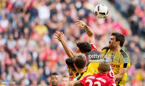 Sokratis Papastathopoulos of Borussia Dortmund challenges Robert Lewandowski of Bayern Muenchen during the Bundesliga match between Bayern Muenchen...
