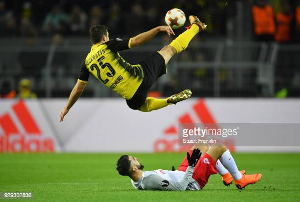 Sokratis Papastathopoulos of Borussia Dortmund clears from Munas Dabbur of Red Bull Salzburg during the UEFA Europa League Round of 16 match between...