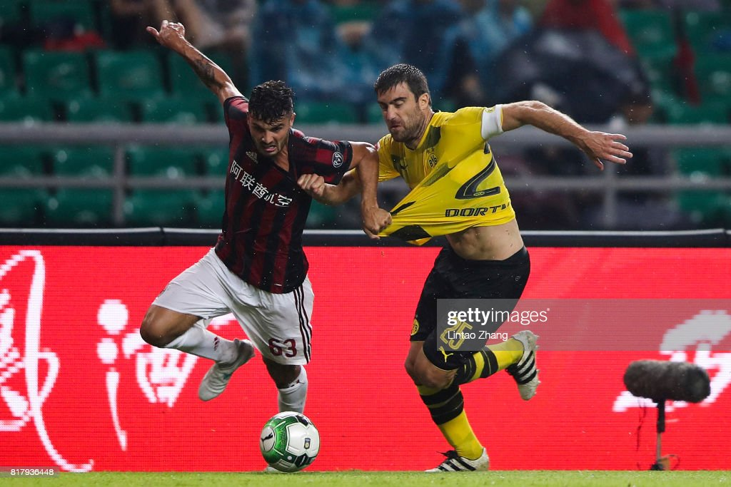 Sokratis Papastathopoulos (R) of Borussia Dortmund competes for the ball with Patrick Cutrone of AC Milan during the 2017 International Champions Cup football match between AC milan and Borussia Dortmund at University Town Sports Centre Stadium on July 18, 2017 in Guangzhou, China.