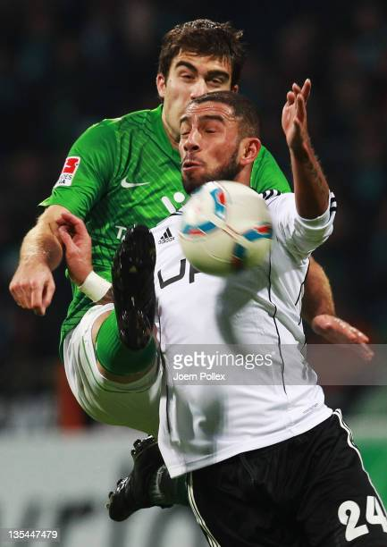 Sokratis Papastathopoulos of Bremen and Ashkan Dejagah of Wolfsburg battle for the ball during the Bundesliga match between SV Werder Bremen and VfL...