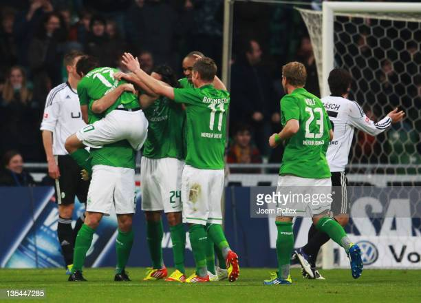 Sokratis Papastathopoulos of Bremen celebrates with his team mates after scoring his team's first goal during the Bundesliga match between SV Werder...