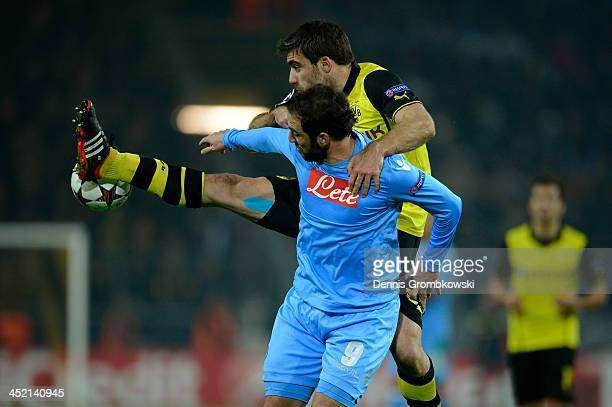 Sokratis Papastathopoulos of Dortmund challenges Gonzalo Higuain of Napoli during the UEFA Champions League Group F match between Borussia Dortmund...