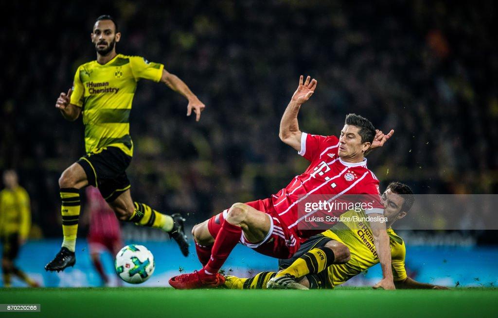 Sokratis Papastathopoulos (R) of Dortmund tackles Robert Lewandowski (C) of Munich during the Bundesliga match between Borussia Dortmund and FC Bayern Muenchen at Signal Iduna Park on November 4, 2017 in Dortmund, Germany.