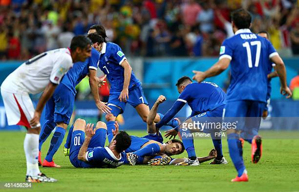 Sokratis Papastathopoulos of Greece celebrates scoring his team's first goal with his teammates during the 2014 FIFA World Cup Brazil Round of 16...