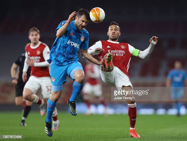 Sokratis Papastathopoulos of Olympiakos battles for possession with Pierre Emerick Aubameyang of Arsenal during the UEFA Europa League Round of 16...