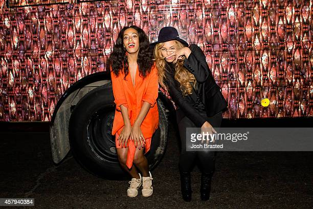 Solange Knowles and Beyonce Knowles pose for a photo against the bounce bus at the cocktail reception for 'Amen Amen The 17 Wards of Wonder' a...