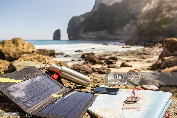Solar battery charger and smartphone on beach, South Coast, Nusa Penida, Indonesia