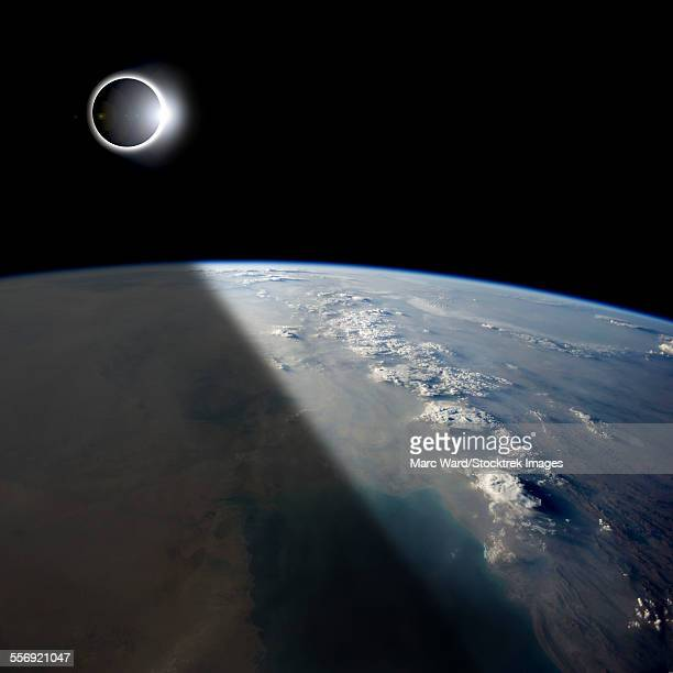 A solar eclipses partially shades the Earth below while the emerging sun lights the remainder of the planet.