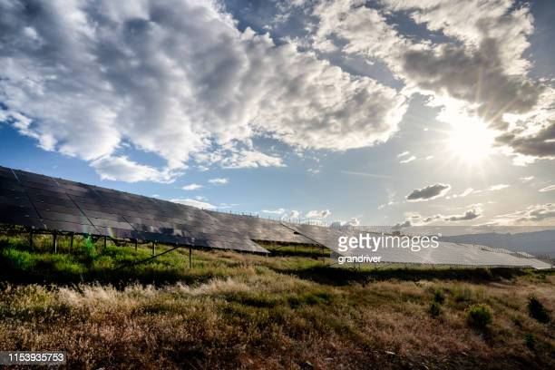 a solar farm in western colorado near sunset with the sun, blue sky and clouds reflecting down on the solar panels - control panel stock pictures, royalty-free photos & images