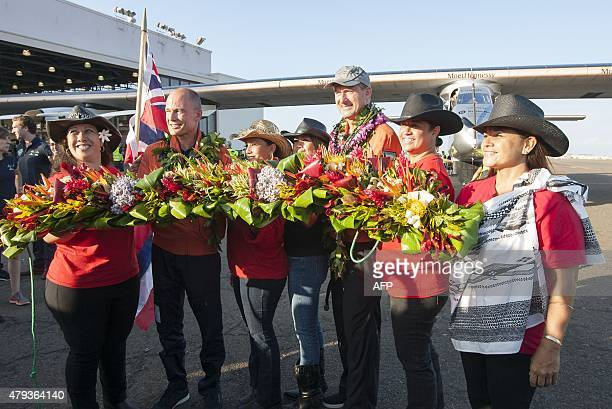 Solar Impulse 2 pilots Bertrand Piccard and Andre Borschberg are greeted by the Hawaiian Pa`u Riders with a Hawaiian lei after Borschberg landed...