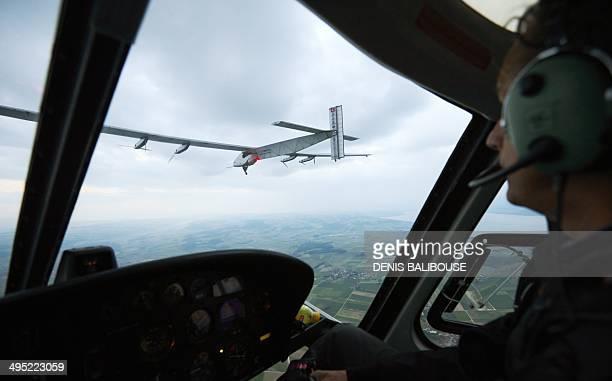 Solar Impulse CEO copilot Andre Borschberg checks from his helicopter German test pilot Markus Scherdel steering the solarpowered Solar Impulse 2...