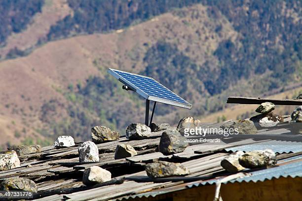A solar panel generates electricity for a village home with a corrugated tin roof held in place by rocks.