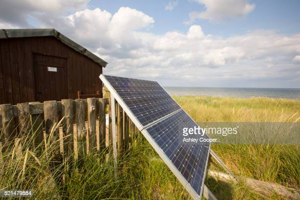 a solar panel generates electricity for an electric fence that protects a nesting terns. - shack stock pictures, royalty-free photos & images