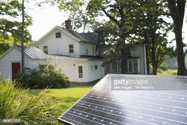 A solar panel in a farmhouse garden.