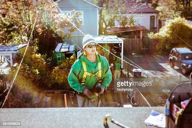 solar panel installation crew member coming up to roof - heshphoto stock pictures, royalty-free photos & images