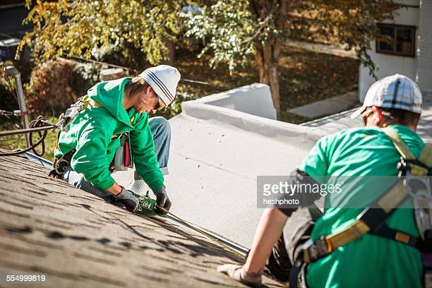 solar panel installation crew members on roof of house - heshphoto stock pictures, royalty-free photos & images
