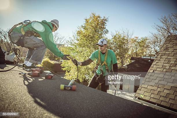 solar panel installation crew members on roof of house - heshphoto photos et images de collection