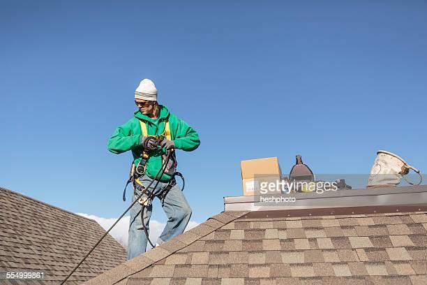 solar panel installation worker on roof of house - heshphoto stock-fotos und bilder
