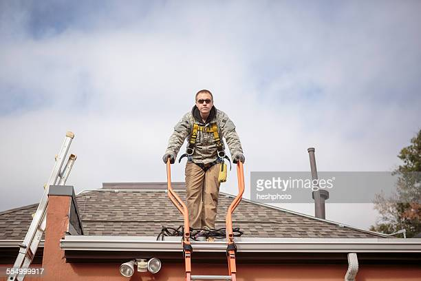 solar panel installation worker on roof of house - heshphoto stock pictures, royalty-free photos & images
