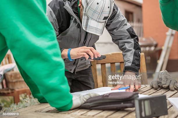 solar panel installation worker photographing paperwork with phone - heshphoto photos et images de collection
