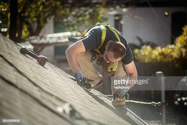solar panel installation worker working on roof of house - heshphoto - fotografias e filmes do acervo