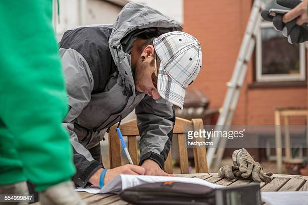 solar panel installation worker writing paperwork - heshphoto stock pictures, royalty-free photos & images