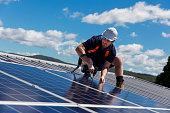 Solar panel installer with drill installing solar panels