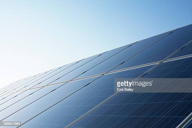 solar panels against blue sky. - solar panels stock photos and pictures