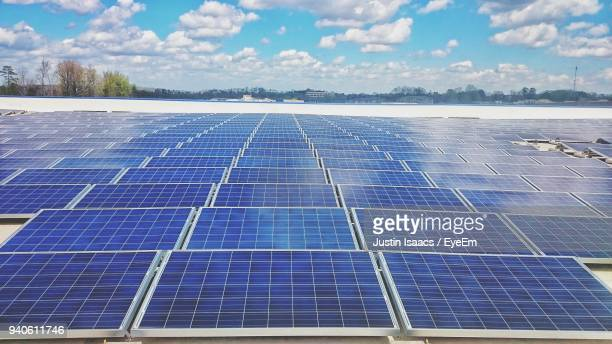 solar panels against cloudy sky - solar powered station stock pictures, royalty-free photos & images