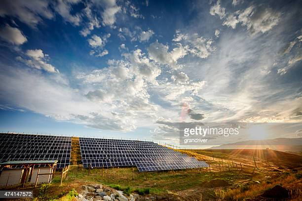 Solar Panels and Green Field Under Dramatic Sky at Sunset