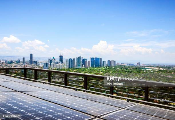 solar panels and manila cityscape under blue sky, philippines - sustainable architecture stock pictures, royalty-free photos & images