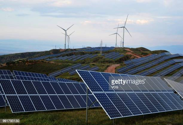 Solar panels and wind turbines are pictured on a barren mountain at Shenjing Village on July 2 2018 in Zhangjiakou Hebei Province of China The...