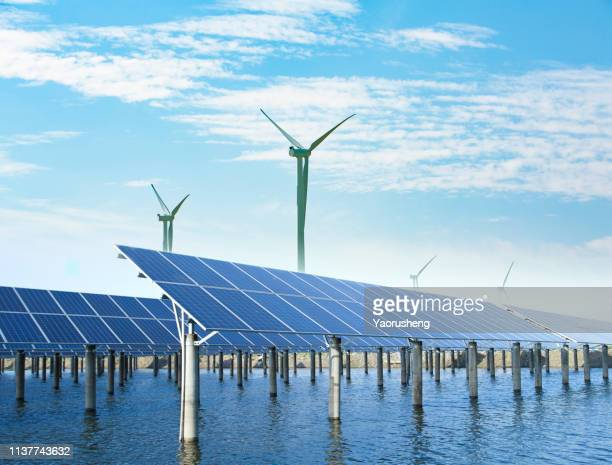 solar panels and wind turbines under blue sky on summer landscape - renewable energy stock pictures, royalty-free photos & images
