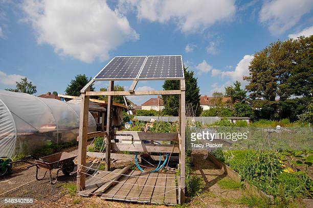 Solar panels charging a solar powered water pump built to recycle water from the otherwise boggy ground for use on the raised vegetable beds poly...
