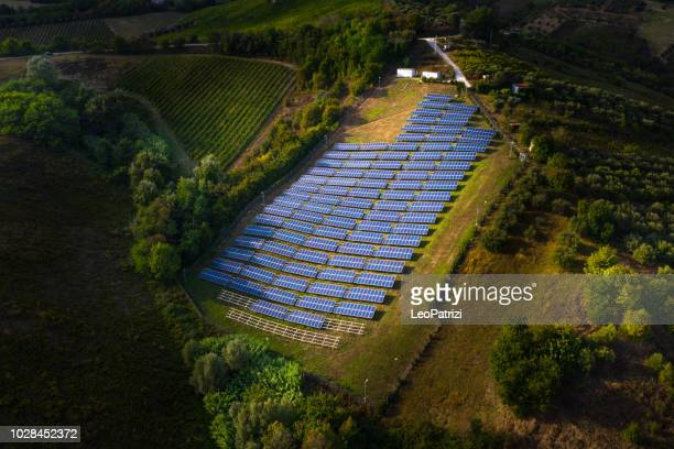solar panels fields on the green hills - economia foto e immagini stock