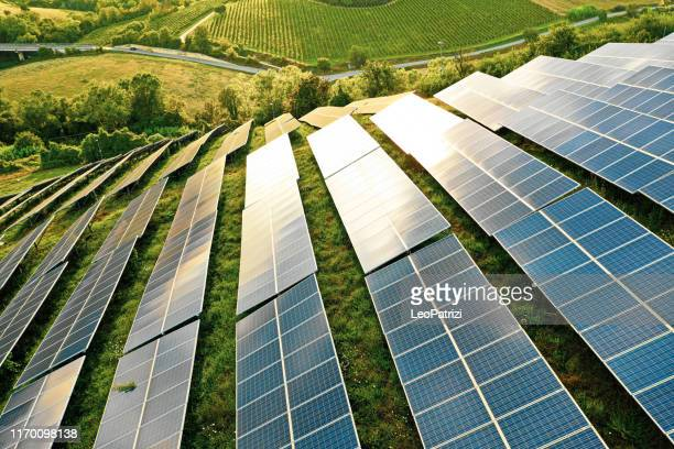 solar panels fields on the green hills - inquinamento ambientale foto e immagini stock