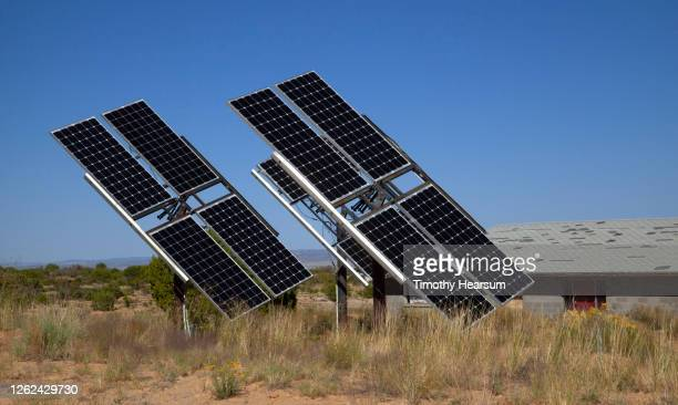 solar panels in a desert yard; barn and blue sky beyond - timothy hearsum stock pictures, royalty-free photos & images