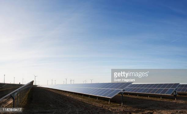 solar panels in a field and wind turbines in the distance - solar equipment stock pictures, royalty-free photos & images